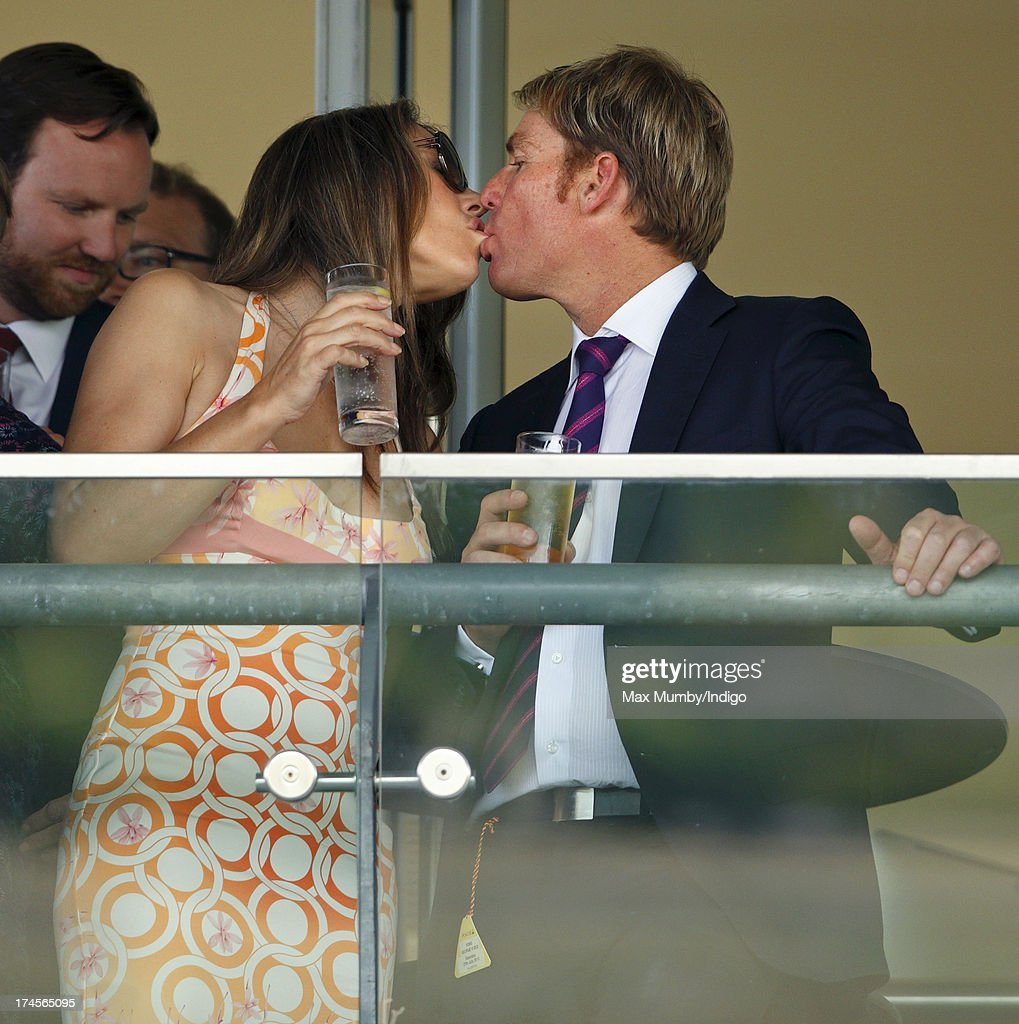 Elizabeth Hurley and Shane Warne kiss whilst watching the racing as they attend the Betfair Weekend, featuring the King George VI and Queen Elizabeth Stakes, at Ascot Racecourse on July 27, 2013 in Ascot, England.