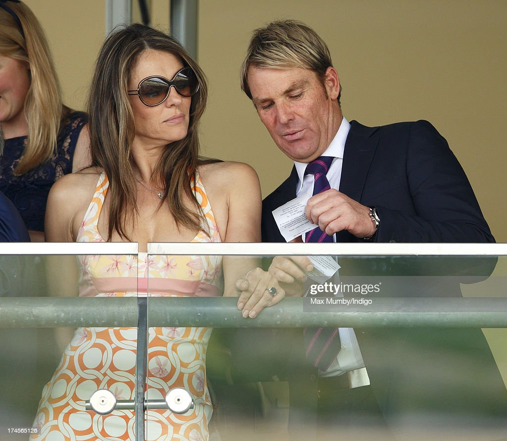 Elizabeth Hurley and Shane Warne watch the racing as they attend the Betfair Weekend, featuring the King George VI and Queen Elizabeth Stakes, at Ascot Racecourse on July 27, 2013 in Ascot, England.