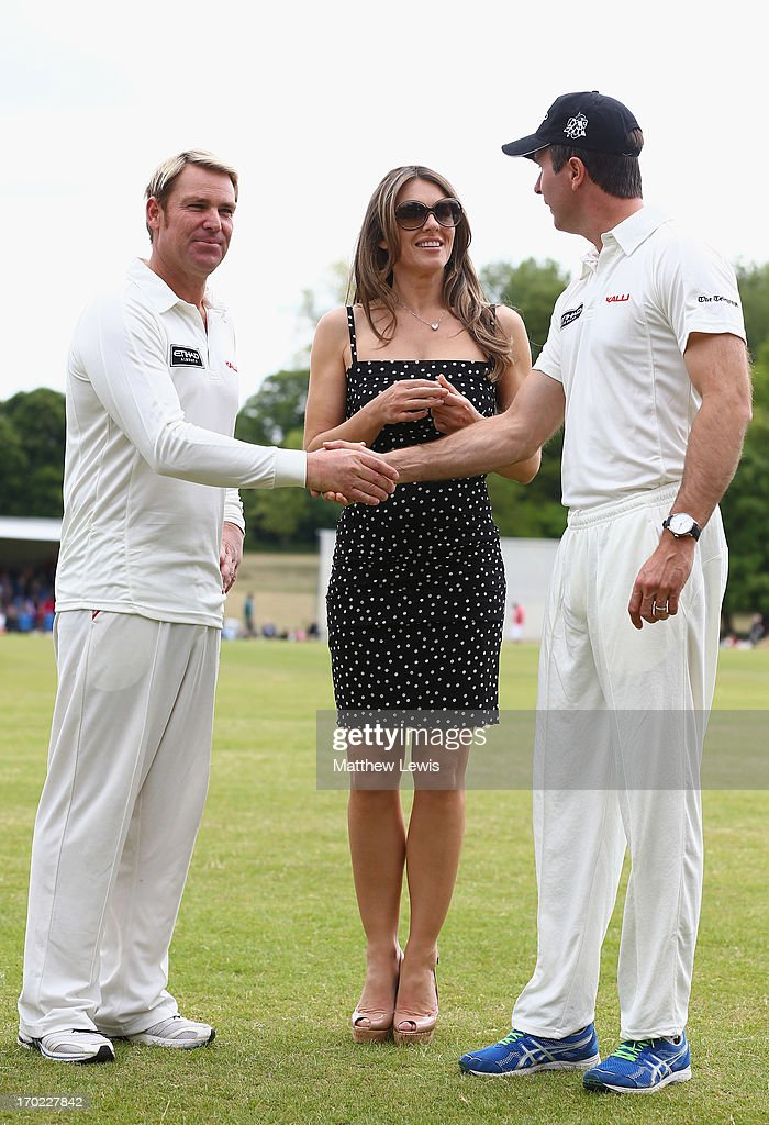 Elizabeth Hurley looks on with Shane Warne and Michael Vaughan during the Shane Warne's Australia vs Michael Vaughan's England T20 match at Circenster Cricket Club on June 9, 2013 in Cirencester, England.