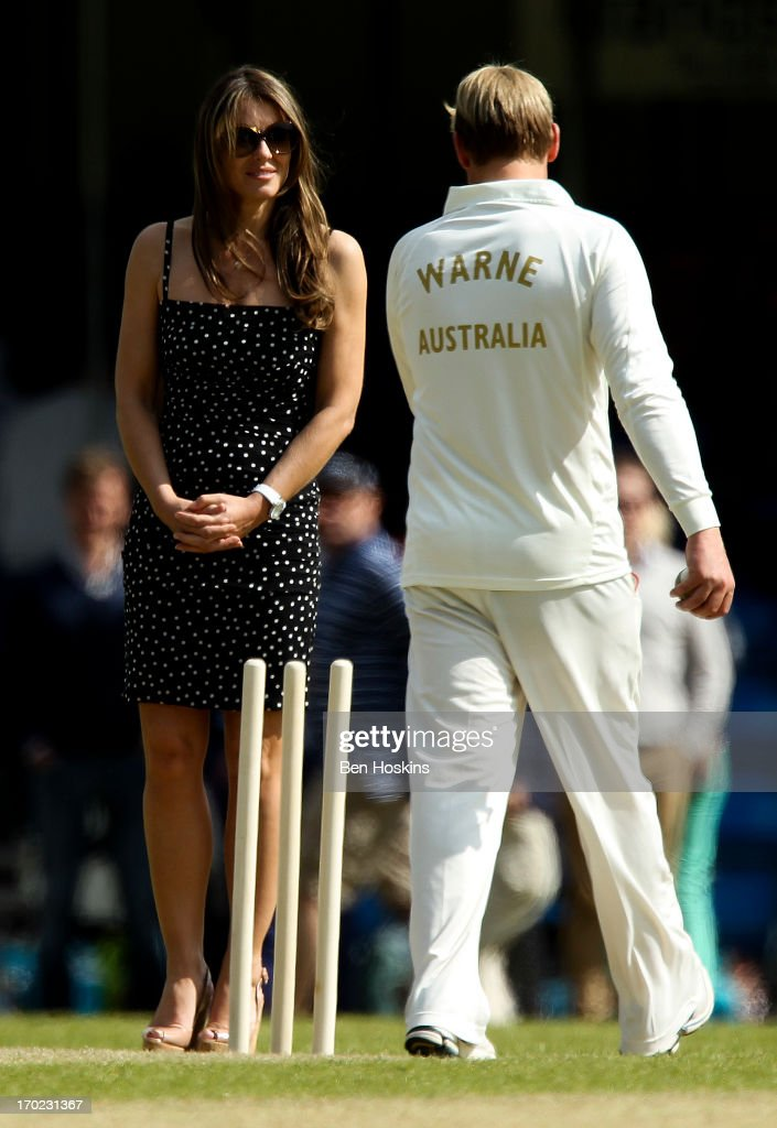Elizabeth Hurley looks on with Shane Warne during Shane Warne's Australia vs Michael Vaughan's England T20 match at Cirencester Cricket Club on June 09, 2013 in Cirencester, England.