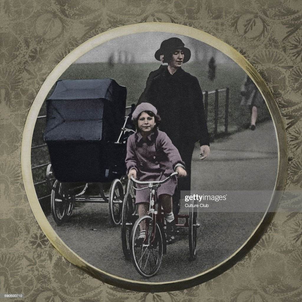 Elizabeth II andPrincess Margaret as children with a nanny Caption reads 'Princess Elizabeth riding her new tricycle in the park with her sister in...