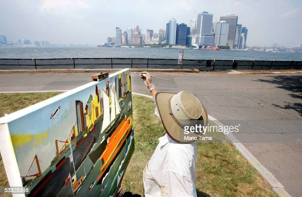 Elizabeth James of Australia paints New York Harbor from Governors Island with the Manhattan skyline behind her August 4 2005 in New York City James...