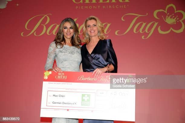 Elizabeth 'Liz' Hurley and Maria Furtwaengler with check during the Mon Cheri Barbara Tag at Postpalast on November 30 2017 in Munich Germany