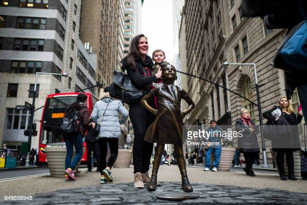 Elizabeth Siegel and her daughter Georgina pose for a photo with 'The Fearless Girl' statue across from the iconic Wall Street charging bull statue...