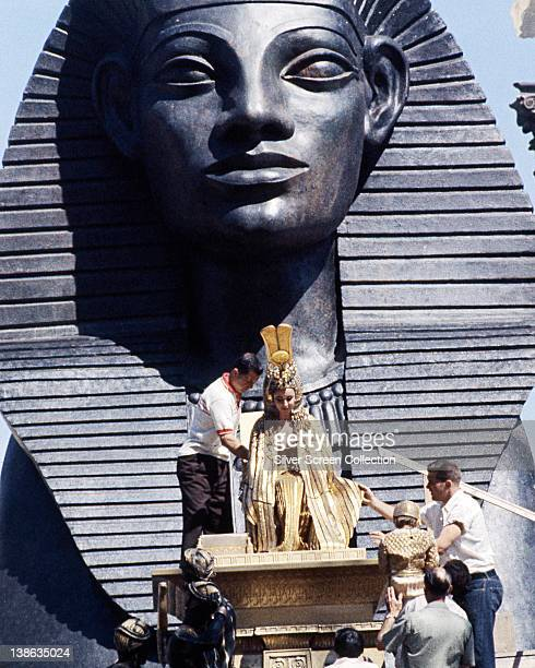 Elizabeth Taylor British actress have her costume of ceremonial robes adjusted as she sits before a large Egyptian statue on the set of the film...