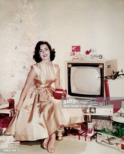 Elizabeth Taylor British actress posing in a yellow dress alongside a white artificial Christmas tree amidst a variety of objects including a...