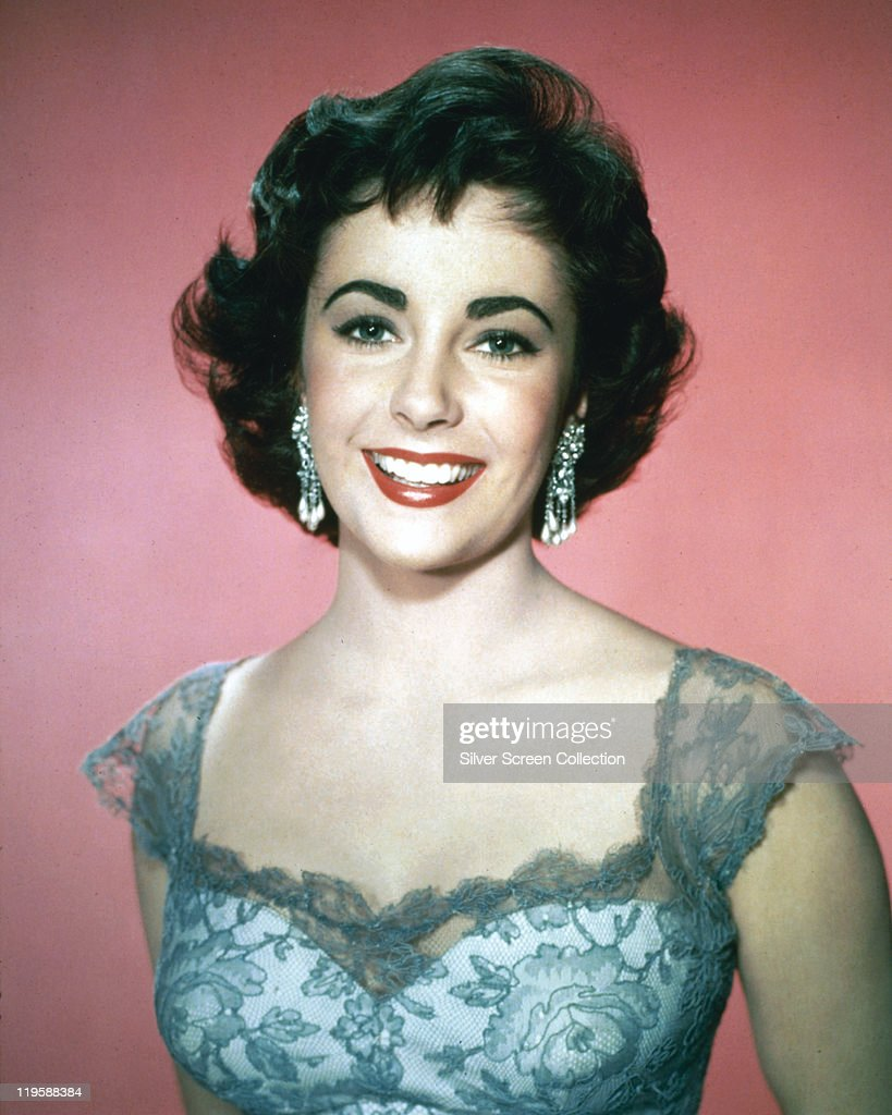 Elizabeth Taylor (1932-2011), British actress, smiling in a studio portrait, against a pink background, circa 1955.