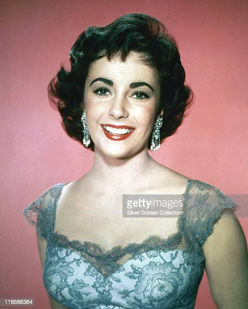 Elizabeth Taylor British actress smiling in a studio portrait against a pink background circa 1955