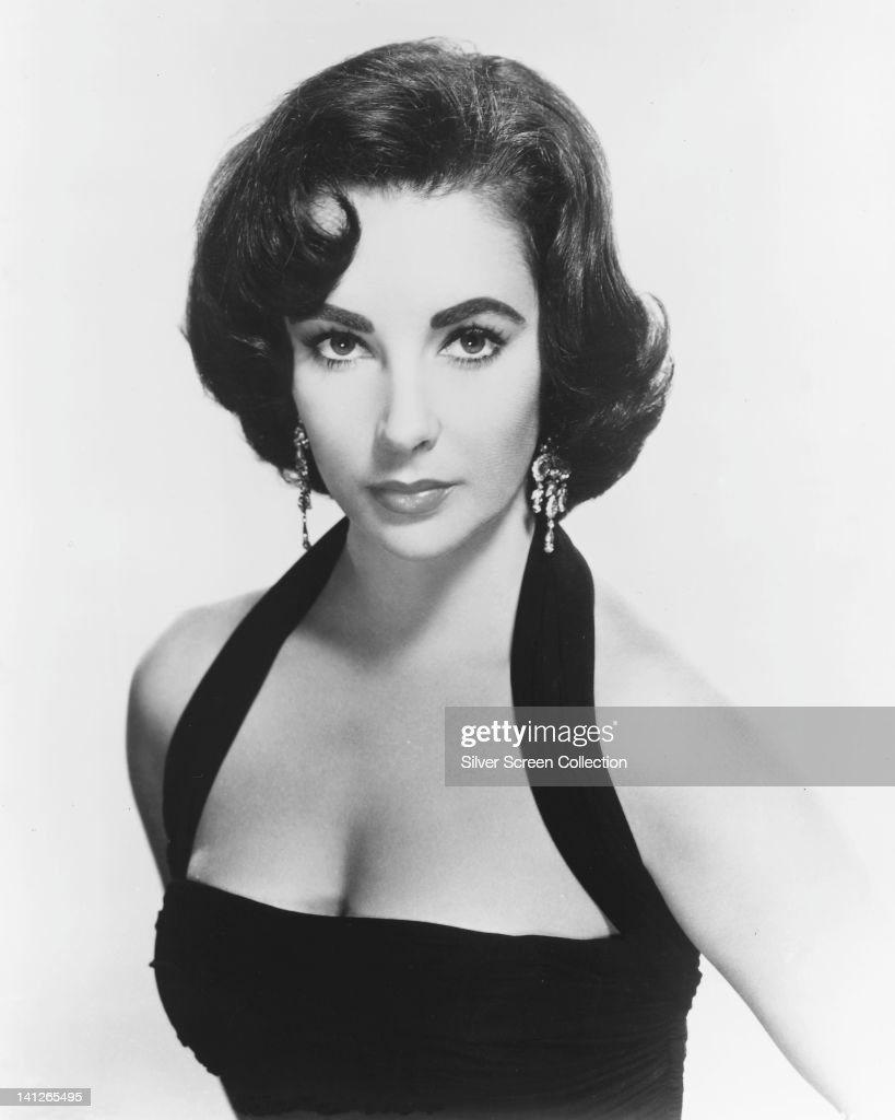 <a gi-track='captionPersonalityLinkClicked' href=/galleries/search?phrase=Elizabeth+Taylor&family=editorial&specificpeople=69995 ng-click='$event.stopPropagation()'>Elizabeth Taylor</a> (1932-2011), British actress, wearing a black halterneck top and drop earrings, looking glamorous in a studio portrait, against a white background, circa 1955.