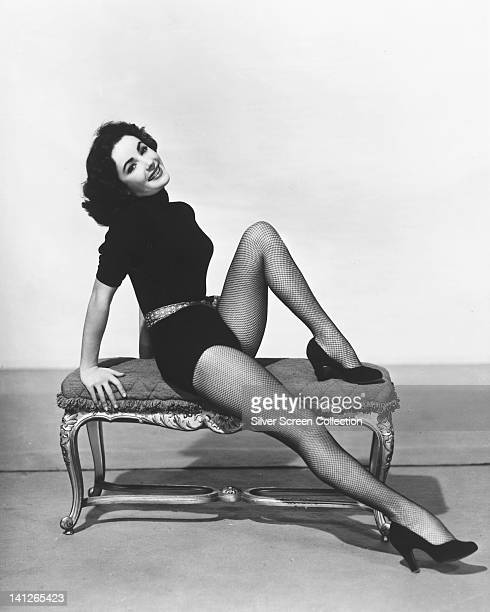 Elizabeth Taylor British actress wearing a black playsuit and fishnet tights posing on a foot stool smiling in a studio portrait circa 1955