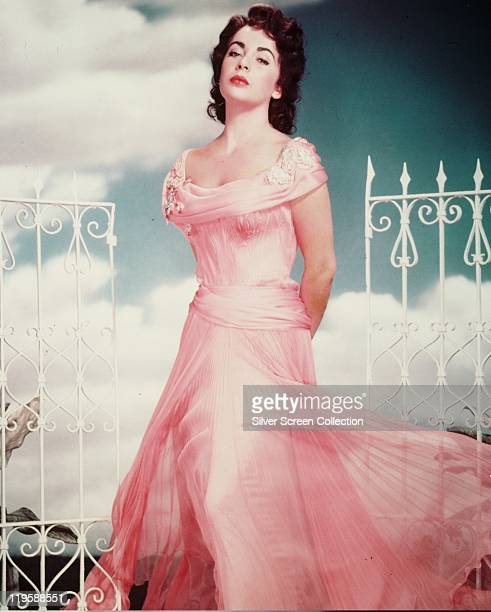 Elizabeth Taylor British actress wearing a long pink gown posing between a pair of white gates in a studio portrait against a background of blue sky...