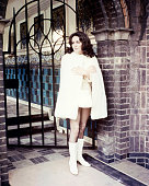 Elizabeth Taylor British actress wearing a short white dress and a white cost with white kneehigh boots in a publicity still issued for the film 'The...