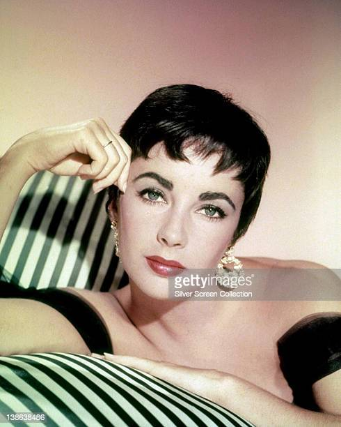 Elizabeth Taylor British actress with cropped hair and wearing circular gold earrings in a studio portrait resting her head on her right hand leaning...