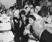 Elizabeth Taylor eating wedding cake at her wedding to Nicky Hilton 6th May 1950 Her new father in law Conrad Hilton looks on and her father Francis...