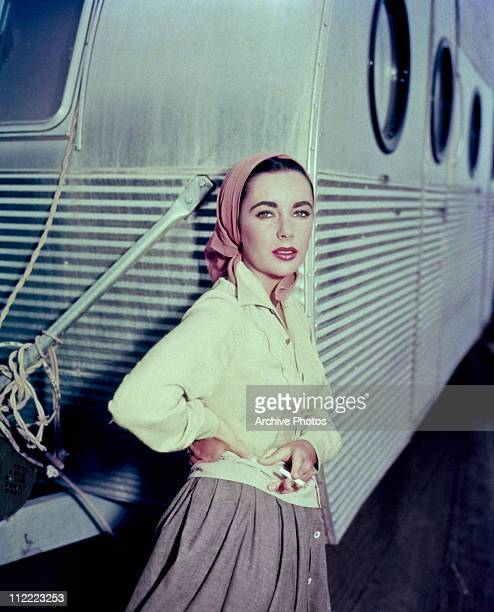 Elizabeth Taylor leaning against a dressing room trailer while smoking a cigarette on the set of director George Stevens's 1956 film 'Giant'