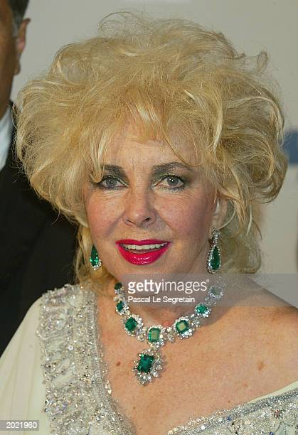 Elizabeth Taylor poses for the cameras as she arrives for the AmfAR Charity Event at the Le Moulin de Mougins during the 56th International Cannes...