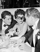 Elizabeth Taylor wearing a party mask but still easily recognizable is the center of attention as Connie Hilton Jr and an unidentifiable man vie for...