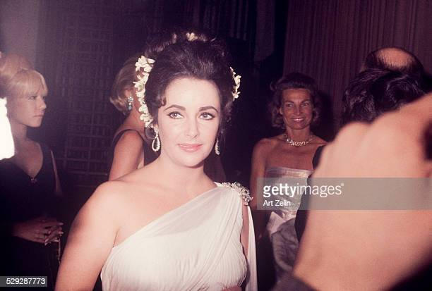 Elizabeth Taylor wearing a white chiffon Grecian dress at a formal event circa 1970 New York