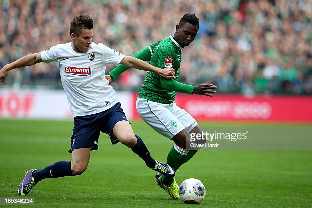 Eljero Elia of Bremen and Felix Klaus of Freiburg compete for the ball during the First Bundesliga match between SV Werder Bremen and SC Freiburg at...
