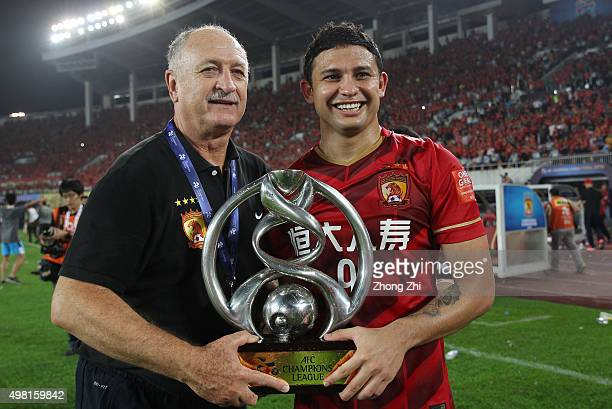 Elkeson De Oliveira Cardoso of Guangzhou Evergrande with Coach Luiz Felipe Scolari of Guangzhou Evergrande pose for photo with trophy after winning...