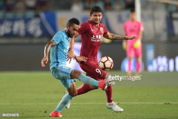 Elkeson of Shanghai SIPG and Alex Teixeira of Jiangsu Suning compete for the ball during 2017 Chinese Super League 15th round match between Jiangsu...