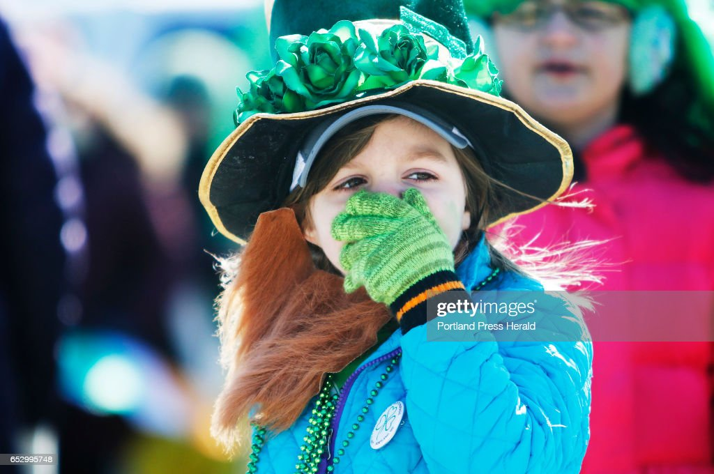 Ella Goldbein, 5, of Saco covers her face from the wind while waiting to line up to march with the Maine Irish Heritage Center in the Irish American Club's annual St. Patrick's Parade on Commercial Street.