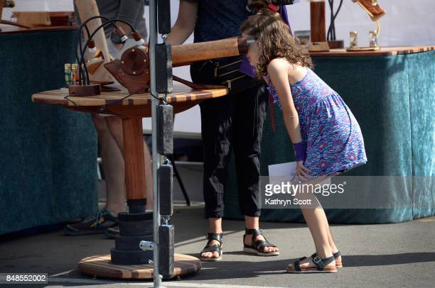 Ella Rusk looks through a handcrafted kaleidoscopes created by artist Henry Bergeson from Conifer CO Crowds gather at the Stanley Marketplace for the...