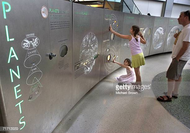 Ella Wolfman and Ronen Wolfman both from Israel walk around the American Museum of Natural Historys Cullman Hall of the Universe August 24 2006 in...