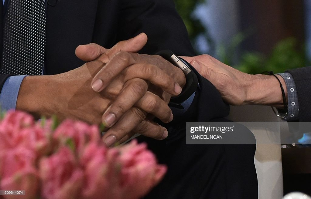Ellen DeGeneres (R) places her hand on the arm of US President Barack Obama while chatting during a break in the taping of The Ellen DeGeneres show at Warner Brothers Studios in Burbank, California on February 11, 2016. / AFP / Mandel NGAN