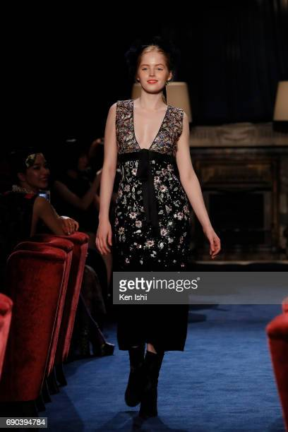 Ellie Bamber showcases designs by CHANEL on the runway during the CHANEL Metiers D'art Collection Paris Cosmopolite show at the Tsunamachi Mitsui...