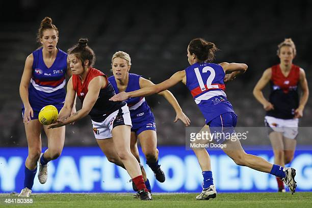 Ellie Blackburn of the Demons handballs away from Renee Forth of the Bulldogs during a Women's AFL exhibition match between Western Bulldogs and...