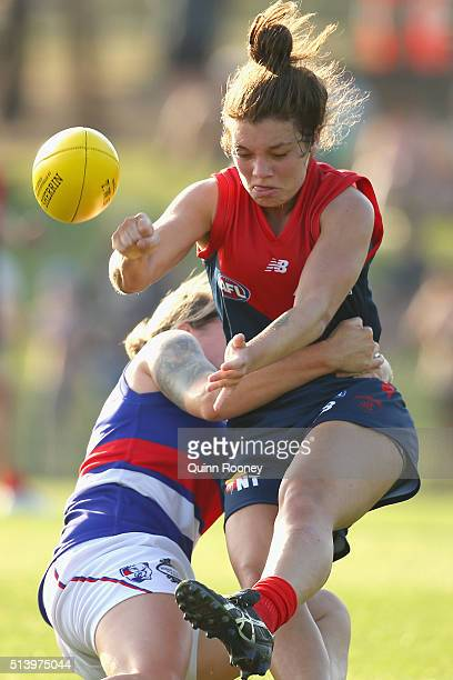 Ellie Blackburn of the Demons handballs whilst being tackled by Hannah Scott of the Bulldogs during the Women's AFL Exhibition Match between the...