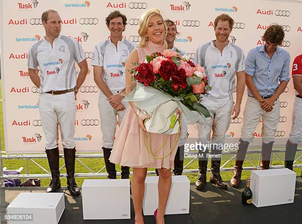 Ellie Goulding is presented with flowers as players Prince William Duke of Cambridge Luke Tomlinson Mark Tomlinson Prince Harry and William...