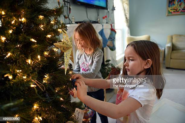 Ellie Haile right helps decorating the Christmas tree at the family house of Kimberly Taylor who opened her home to housemate Mitzi Hellmer in...