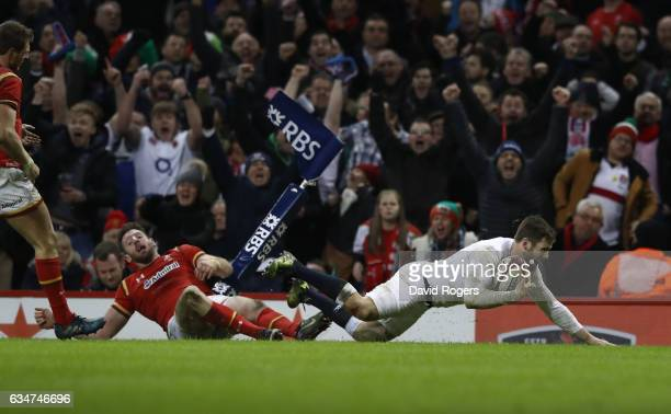 Elliot Daly of England dives past Alex Cuthbert of Wales to score the match winning try during the RBS Six Nations match between Wales and England at...
