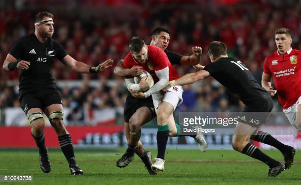 Elliot Daly of the Lions is tackled by Anton LienertBrown and Beauden Barrett of the All Blacks during the third test match between the New Zealand...