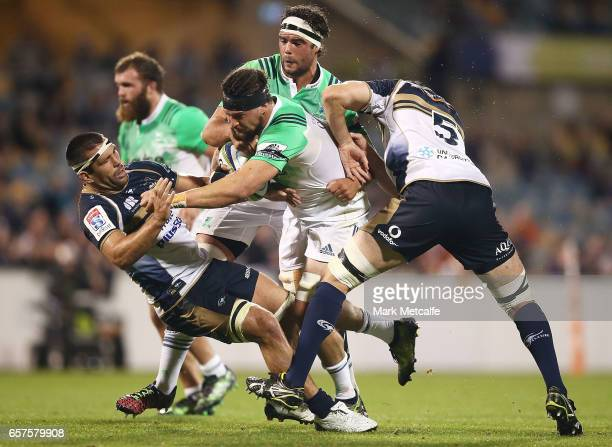 Elliot Dixon of the Highlanders breaks through the tackles of Sam Carter of the Brumbies and Chris Alcock of the Brumbies during the round five Super...