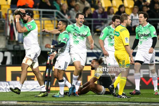 Elliot Dixon of the Highlanders celebrates his try with teammates Aaron Smith and Ben Smith during the round four Super Rugby match between the...