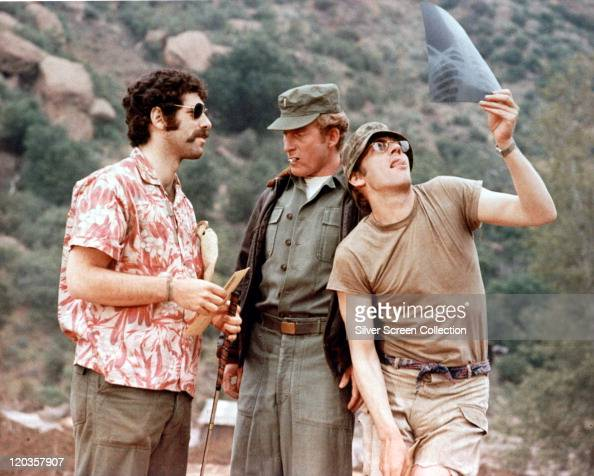Elliot Gould US actor talking with a uniformed officer smoking a cigarette and Donald Sutherland Canadian actor examining an xray in a publicity...