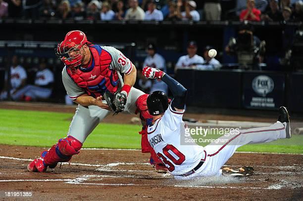 Elliot Johnson of the Atlanta Braves scores a secondinning run against Erik Kratz of the Philadelphia Phillies at Turner Field on September 26 2013...
