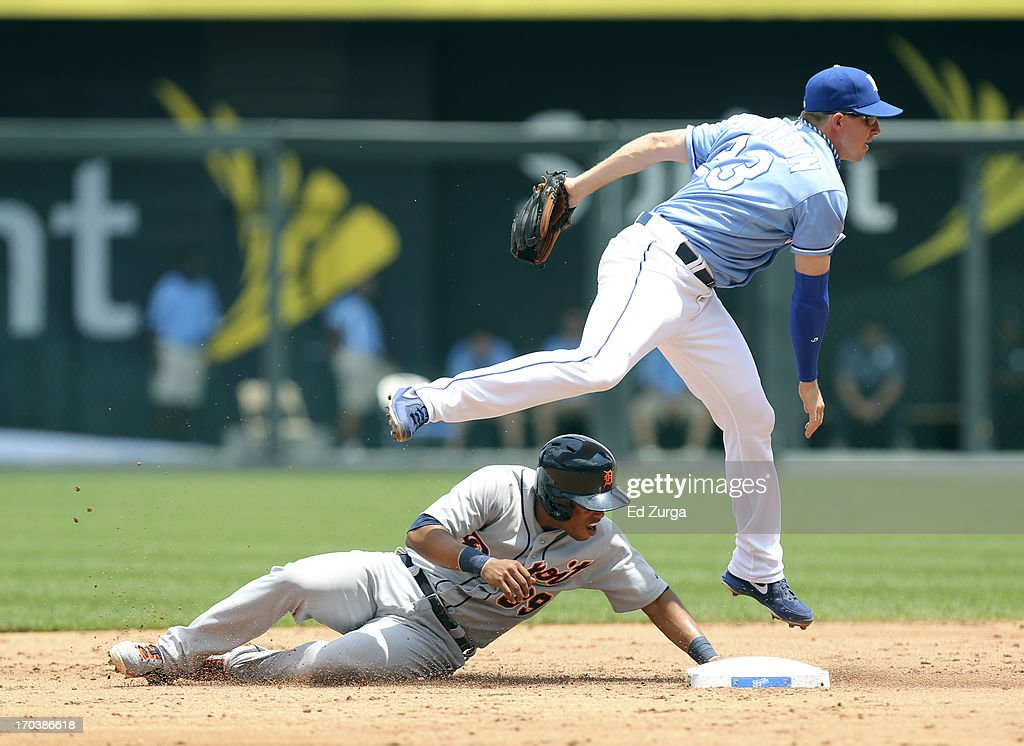 Elliot Johnson #23 of the Kansas City Royals leaps over <a gi-track='captionPersonalityLinkClicked' href=/galleries/search?phrase=Ramon+Santiago&family=editorial&specificpeople=2984417 ng-click='$event.stopPropagation()'>Ramon Santiago</a> #39 of the Detroit Tigers as he throws to first to complete a double play in the third inning at Kauffman Stadium on June 12, 2013 in Kansas City, Missouri.