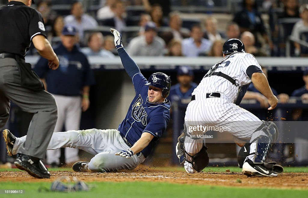 Elliot Johnson #9 of the Tampa Bay Rays slides home safely ahead of the tag from Russell Martin #55 of the New York Yankees to score a seventh inning run at Yankee Stadium on September 14, 2012 in the Bronx borough of New York City.