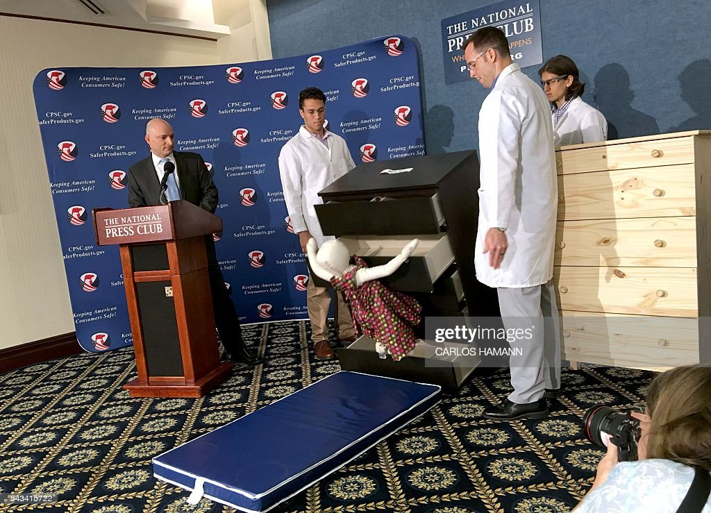 Elliot Kaye (L), chair of the Consumer Product Safety Commission (CPSC) and CPSC employees watch as a 28-pound (13 kilo) dummy(C) falls over and under IKEAs Malm model chest of drawers, during a live demonstration at the National Press Club in Washington, DC 28 June, 2016. Furniture giant Ikea said June 28 it would recall its hugely popular Malm model of chest of drawers in the US and Canada after six children in the US were crushed to death when the chests tipped over. In 2015, Ikea launched a campaign in the US and Canada to encourage owners of the Malm chests of drawers to anchor them to the wall. / AFP / Carlos HAMANN