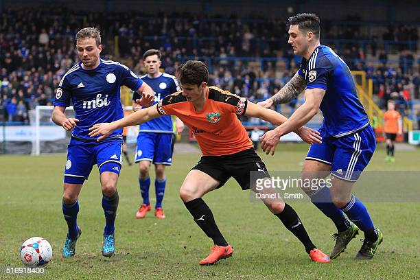 Elliot Osborne of Nantwich Town FC tries holding off Matty Brown and Kevin Roberts of FC Halifax Town during the FA Trophy Semi Final Second Leg...