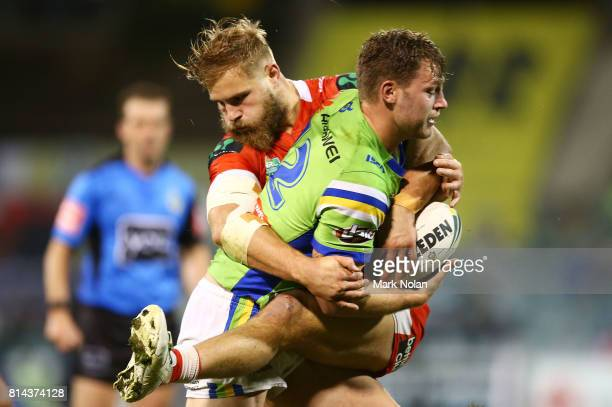 Elliot Whitehead of the Raiders is tackeld by Jack De Belin of the Dragons during the round 19 NRL match between the Canberra Raiders and the St...