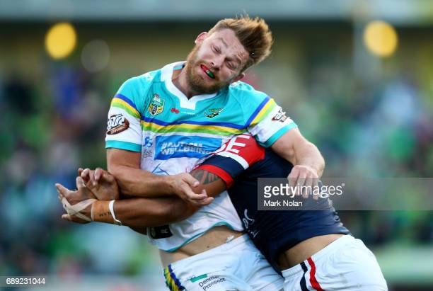Elliot Whitehead of the Raiders is tackled after offloading during the round 12 NRL match between the Canberra Raiders and the Sydney Roostrers at...