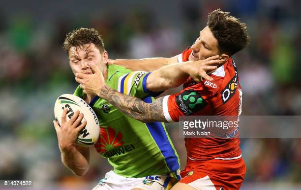 Elliot Whitehead of the Raiders is tackled by Gareth Widdop of the Dragons during the round 19 NRL match between the Canberra Raiders and the St...