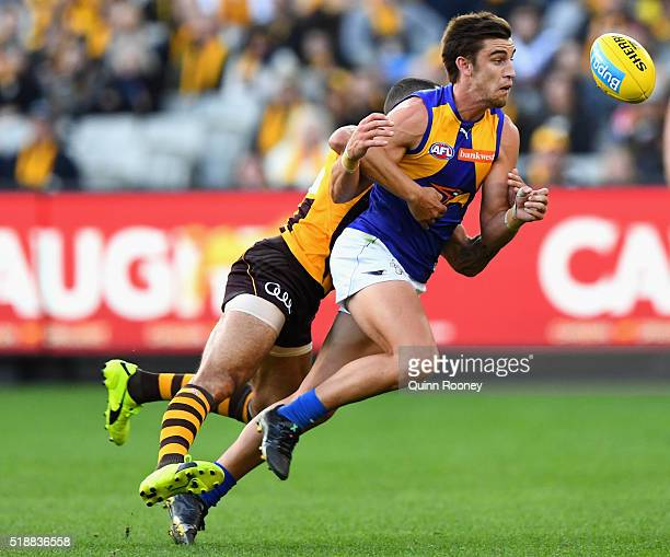 Elliot Yeo of the Eagles handballs whilst being tackled by Shaun Burgoyne of the Hawks during the round two AFL match between the Hawthorn Hawks and...