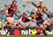 Elliot Yeo of the Eagles runs with the ball away from a diving Craig Bird of the Bombers during the NAB Challenge AFL match between the West Coast...