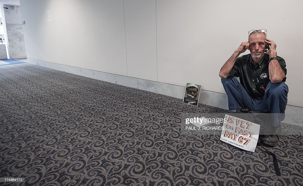 Elliott Adams, a US military veteran, on his 67th day of a hunger strike in support of closing the US Guantanmo Naval Base detention facility, conducts a telephone media interview in a empty lobby just outside and during the US Senate Judiciary Committee, The Constitution, Civil Rights and Human Rights Subcommittee hearing on 'Closing Guantanamo: The National Security, Fiscal, and Human Rights Implications.', July 24, 2013, in Washington, DC. Several of the protesters have been conducting hunger strikes. AFP PHOTO/Paul J. Richards